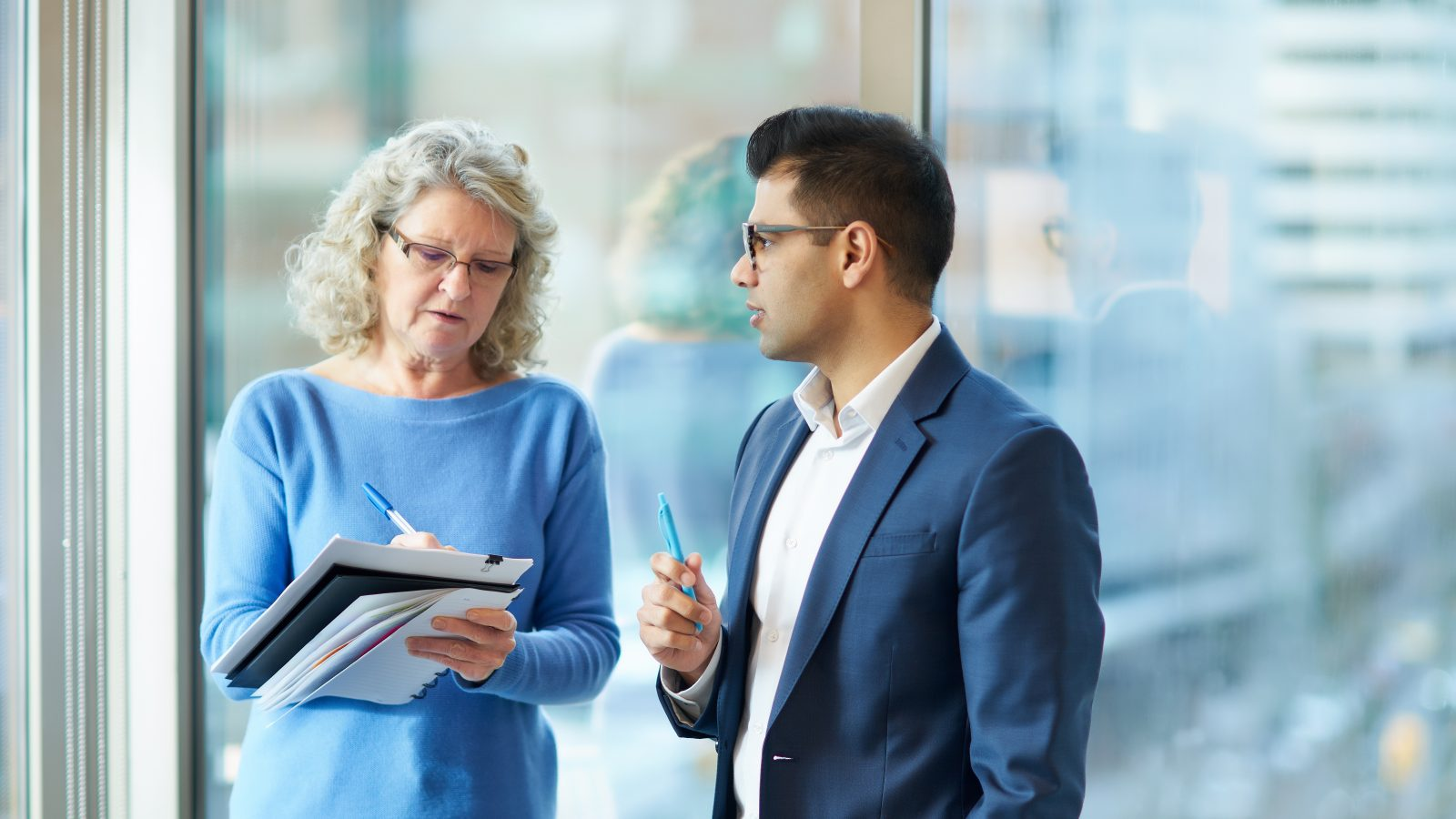 man speaking to woman taking notes in front of window